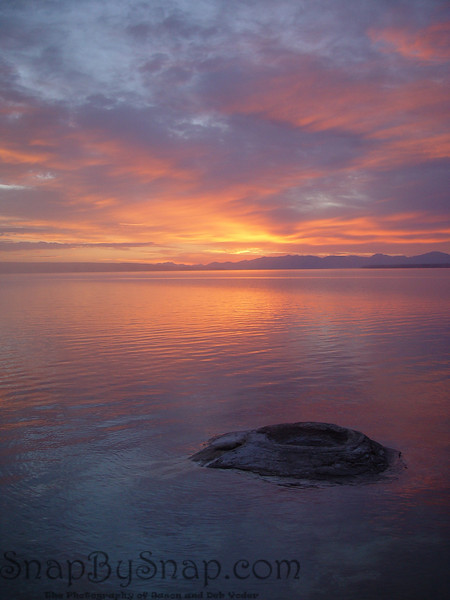 A colorful sunrise over Yellowstone Lake with Fishing Geyser in the foreground.
