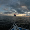 Sunrise from the dive boat off the western coast of Thailand.  A tiny Thai flag flaps at the bow; Andaman Sea, near the border with Burma.