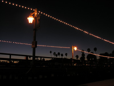 Strings of lights along Stearn's Wharf, a local landmark and tourist attraction that offers shopping, restaurants, views, and sights of unloading fishing boats.