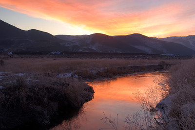 Colorful sunrise over river through icy reeds and buckwheat.