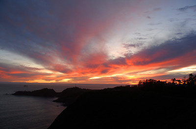 © Joseph Dougherty.  All rights reserved.   Colorful sunset over the Marin Headlands and Point Bonita Lighthouse, with container ship sailing out of San Francisco Bay.