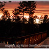 A sunset sets the sky aglow, as viewed from my deck; LED Christmas lights sparkle here and there on the deck.