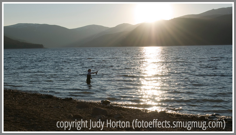 A young boy fishes in a Colorado lake at sunset