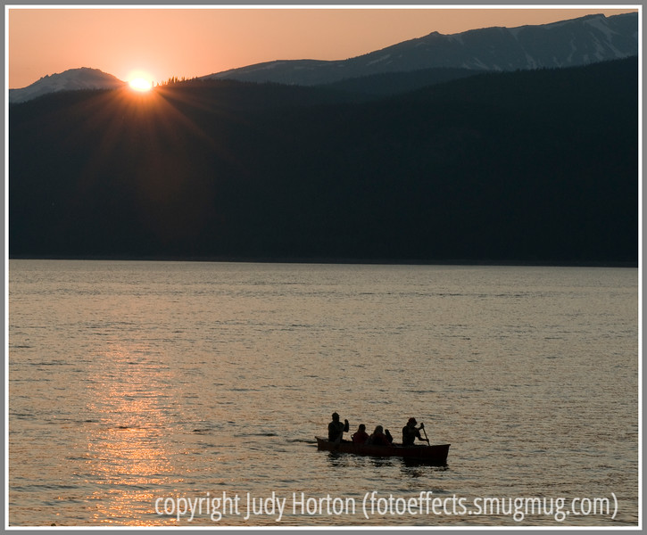 As the sun sets on Turquoise Lake in Colorado near Leadville, some people in a canoe head for shore.
