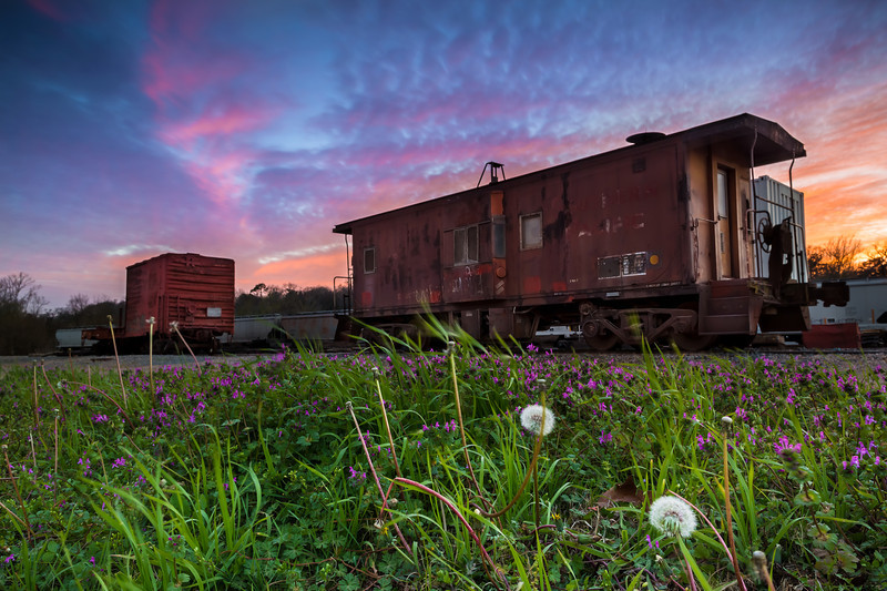 """Colorful Caboose Revisited, Nacogdoches TX  I found out about a cool East Texas photo competition yesterday and started deciding which three photos to enter.  I think this photo makes a good entry because it's pretty and showcases some of Nac's railroad history.  I reprocessed it using Photoshop, and this is the second photo I've actually exported out of Photoshop.  More on Photoshop below.  The second photo I chose is <a href=""""http://smu.gs/YC4usm"""">this beauty</a> of the Japanese Maples in the SFA Arboretum, which I have a 20x30"""" print of hanging in our bedroom and really love it.  For my third choice I want to enter one of my Lake Sam Rayburn photos, and have tentatively chosen <a href=""""http://smu.gs/12opLOk"""">this one</a> of the warm grass on our beach at sunset.  But I don't know, this isn't my personal favorite, it's just the one I think will be most useful for the Texas Forest Trail Region website.  My current favorite of Sam Rayburn is this <a href=""""http://smu.gs/12xyVrY"""">blue hour beauty</a>, but I think it might be too abstract for this competition.  Another Sam Rayburn favorite is this <a href=""""http://smu.gs/15etLzD"""">this colorful long exposure</a>, but again I think the long exposure might be too abstract.  Lastly, my all time favorite Sam Rayburn photo is <a href=""""http://smu.gs/OtdgdL"""">this red and pink long exposure</a>.  Can you help me decide or give any other tips and tricks for entering photo contests?  This will be my first.  This photo is a reprocessed version of my original <a href=""""http://smu.gs/12z04eh"""">Colorful Caboose photo</a>.  I liked the previous version, but wish I had used a smaller aperture to achieve a longer depth of field and sharper focus on the caboose.  I also didn't like how underexposed the caboose is, mostly due to the graduated neutral density filters I used to reduce the exposure in the sky.  So what did I do to fix it up a little?  I went back to the archives to see if I had an overexposed exposure from the same spot, and I """