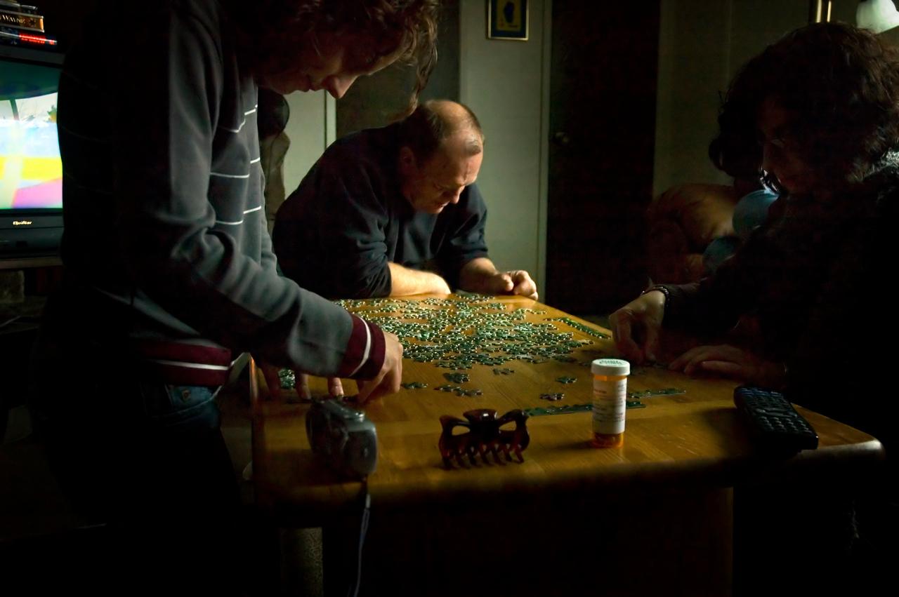 Corey assembles a puzzle with her parents