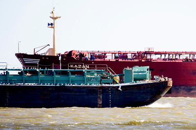 A bird-draped barge passes in front of a Tanker.