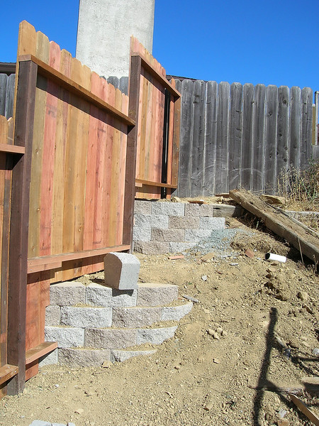 Day 3:  The retaining wall blocks wrapping around under the fence will form the left side of a stairway to a new gate between our two back yards.