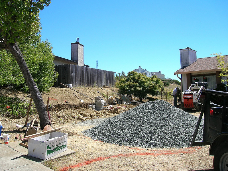 Day 1:  Dead retaining wall and fence are gone, the trench is dug for the new retaining wall, a mountain of gravel awaits the teeth of the cool little hand-driven Bobcat ...