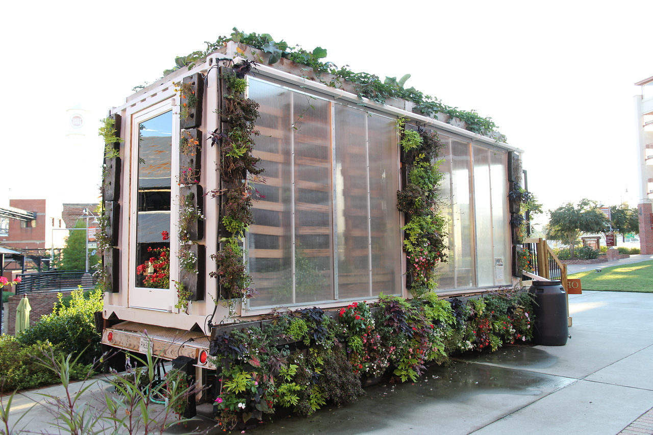 """The """"Farmery"""" is an open air market made out of a converted  20 X 8 foot shipping container with living wall planters hanging outside."""