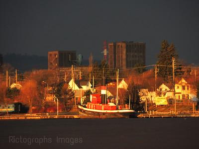 Golden Light Shining On The Kam River Park & The James Whalen Tug Boat