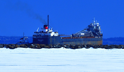 Tug Boat Guiding Freighter Through Ice And Into Port