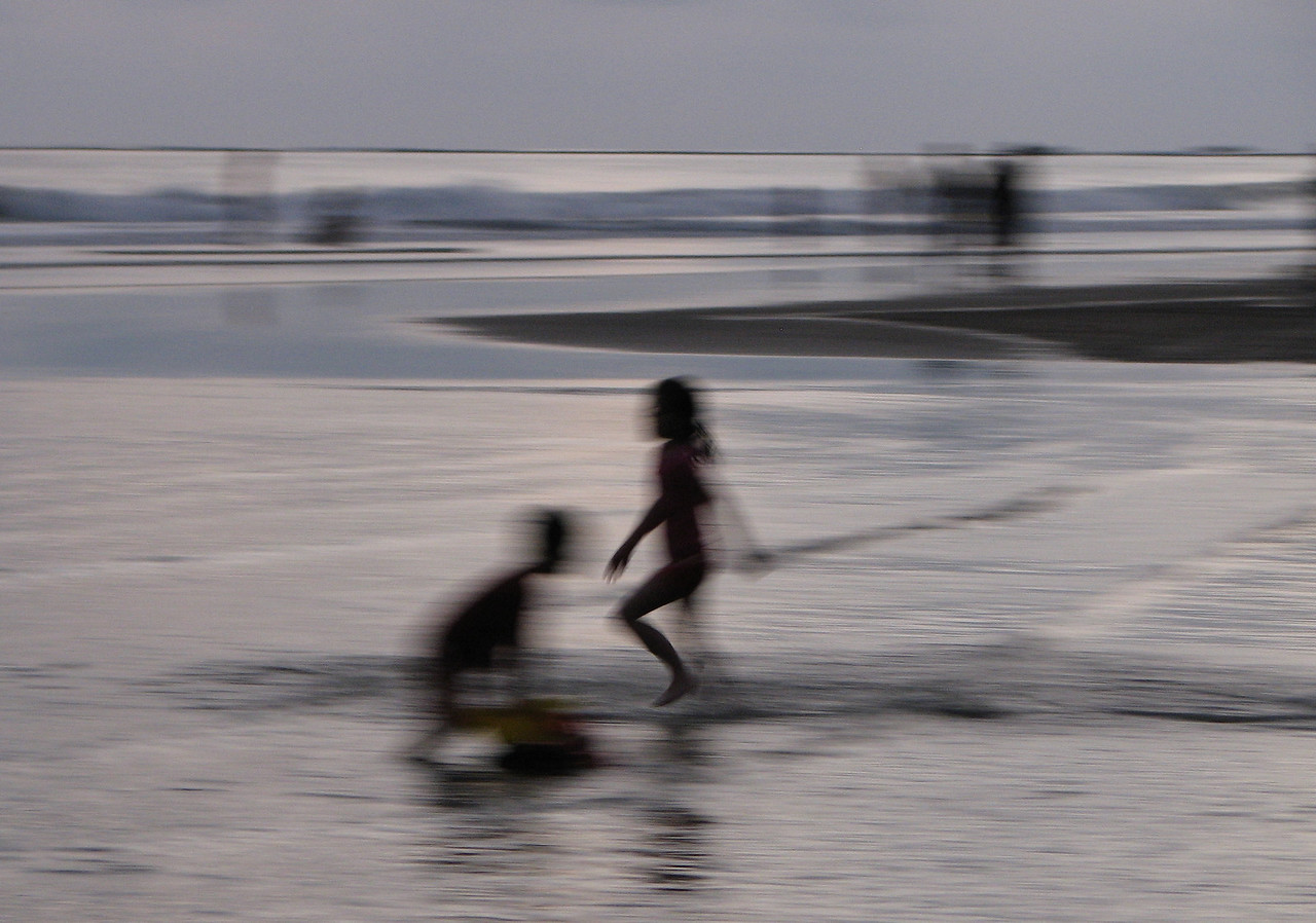 Children playing on the beach at Uvita, at dusk on New Years Day