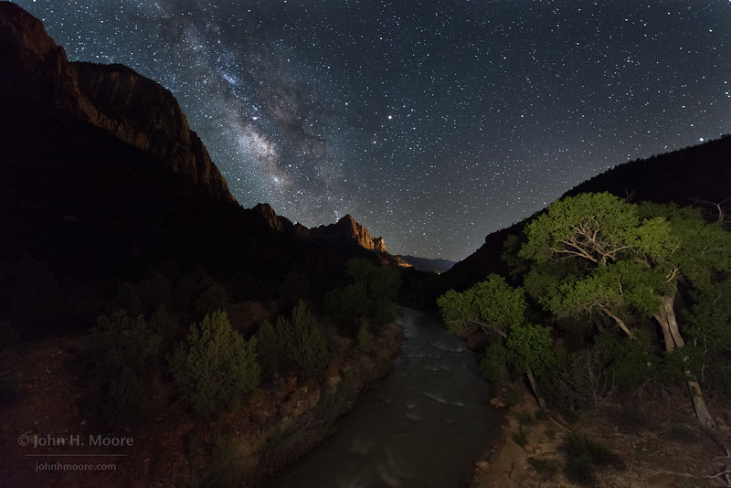 Looking down the Virgin River in Zion National Park towards The Watchman, lit by the lights of Springdale, Utah, under the night sky.  Utah, USA.