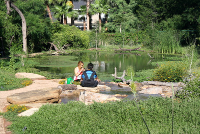 Two young people find a comfortable place to enjoy the new Ruby Pond at Quinta Mazatlan.  The pond was constructed as an educational tool where everyone can learn about the cycles of life around natural water features.