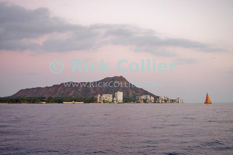 Apartment buildings and condominiums flank the slopes of Diamond Head.  Kapiolani Park and Waikiki beach flank the mountain to the left.  Waikiki, Honolulu, Oahu, Hawaii.  © Rick Collier<br /> <br /> <br /> <br /> <br /> <br /> <br /> <br /> Hawaii Hawai'i Oahu Waikiki sunset sun set sail sailboat sea ocean Diamond Head extinct volcano apartment building condomunium condo Kapiolani Park beach