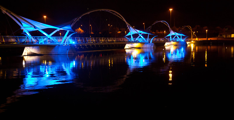 An artsy bridge over the Tempe Town Lake, at night.