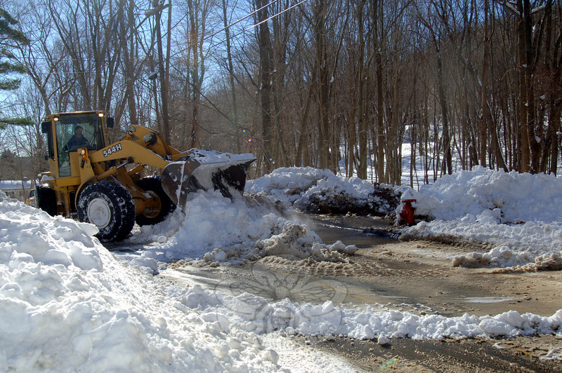 Town crews tried to control the heavy flow of water from a hydrant on West Street that a plow had accidentally clipped Wednesday morning by piling snow around the immediate area with a backhoe.  (Bobowick photo)