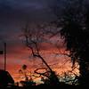 Reddish orange clouds behind anemometer before dawn