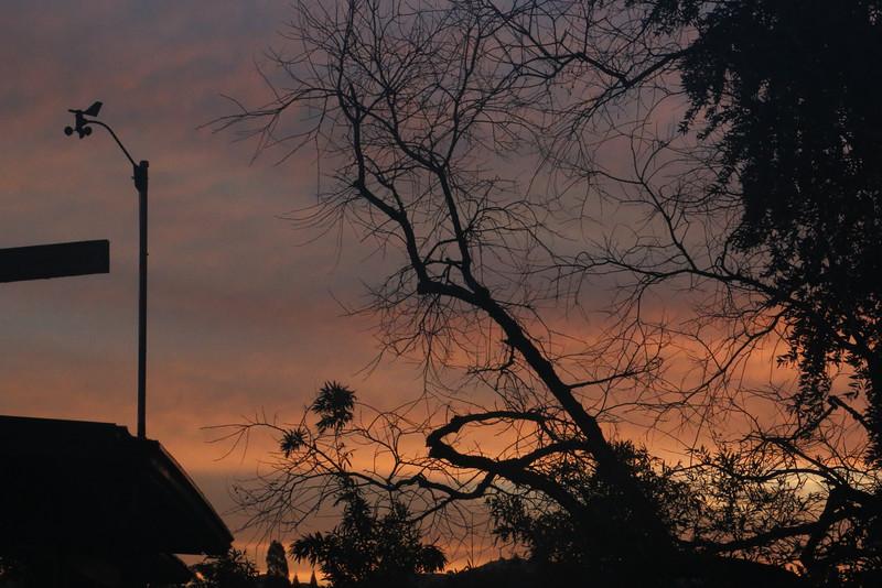 Orange cloud bands behind anemometer before dawn