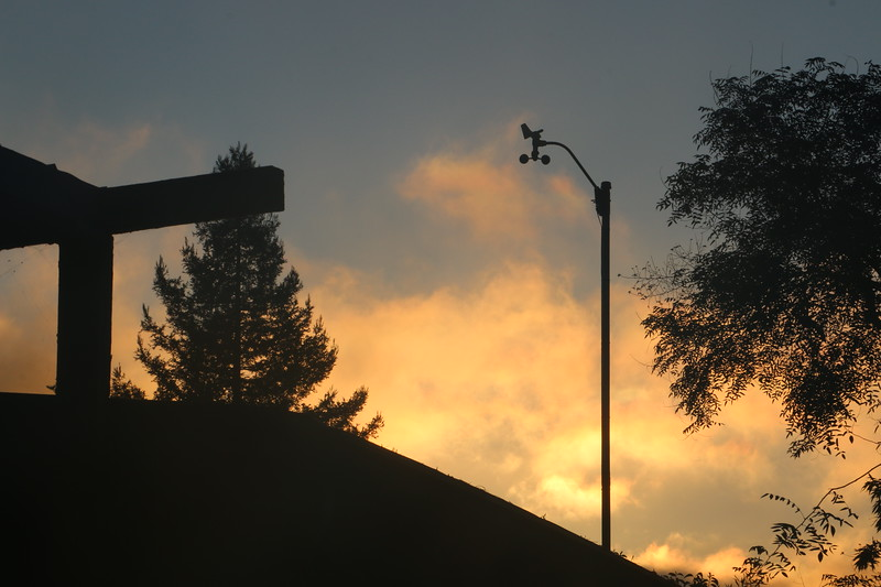 Colorful marine clouds behind anemometer at dawn