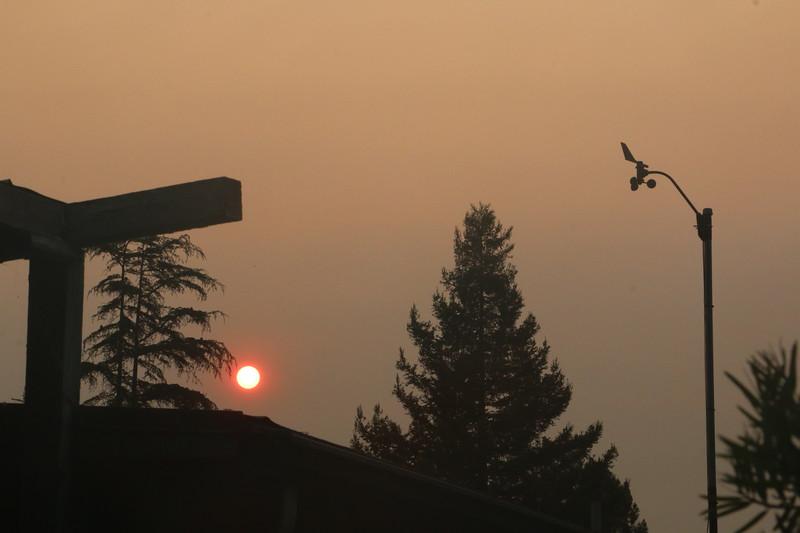 Sun through smoke near anemometer after dawn