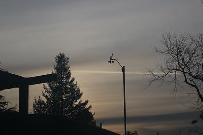 Grey cloud bands behind anemometer at dawn