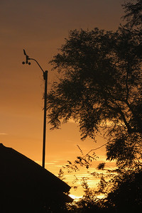 Fiery sky behind anemometer at dawn