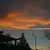 Redish orange clouds behind anemometer at dawn