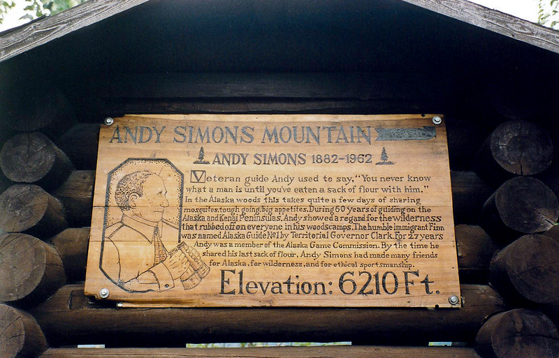 AK-1999.7#032. Andy Simons Memorial plaque. Andy was one of my hero's and one of the greatest Alaska Pioneers. A person needs to read Hunting the Alaska Brown Bear and Hunting the Kenai Peninsula, both authored by John W. Eddy to really understand and know how special Andy was. Located in the parking area where you can view Andy Simonds Mountain from near Primrose Campground, Kenai Peninsula, Alaska.