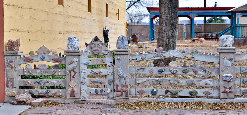 "NM-MA-2019.11.11#2875.3. The Folk Art fence that was decorated by Clem ""Pop"" Shaffer. Mountainair New Mexico. Like on his Hotel, and Restaurant building, the symbol at the bottom right of the gate is not a Nazi Swastika. It's a Navajo ""Whirling Log"" that is a symbol of peace and goodwill."