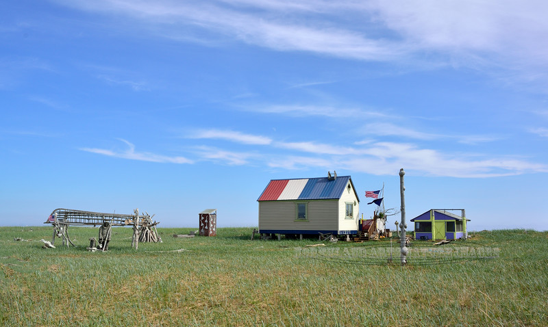 AK-SPns-2015.6.24#361.1x. An Inupiaq Eskimo subsistence fishing and hunting camp along the shore of Norton Sound. Even though the camp is more modern they have a display of a traditional Eskimo Walrus/Seal Skin Boat frame with an Eskimo hunter in front of it. Viewed from the Nome to Council road on the Seward Peninsula Alaska.