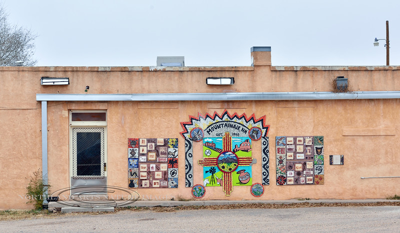 NM-MA-2019.11.11#2810.2. Wall Art of quilt like patterns composed of photographs and mosaic symbols and a center piece celebrating Mountainair  with symbols that dipict things found in the area and commemorate the founding of the town in 1903. Mountainair, New Mexico.