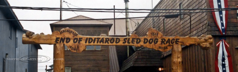 AK-SPn-2001.6#3087.3. The Burled Arch. End of the Iditarod Sled Dog Race on Front Street in Nome, Alaska. In front of an alley for storage till race time.