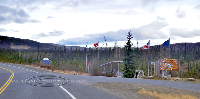 CANYK-2017.5.14#053.3. The rest stop with country flags for the United States, Alaska and the Yukon Territory, and Canada border. Unfortunately  late at night with pretty dank light.