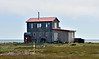 AK-SPns-2015.6.24#121.1. A view of an unusually large home looking out over Norton Sound. Most of the cabins and homes are fishing and hunting camps out here. Viewed off the Nome to Council road, Seward Peninsula Alaska.