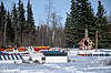 AK-E5-1984.3#00069.3. Athabaskan Spirit Houses in front of the small Russian Orthodox Chapel at Eklutna Alaska.