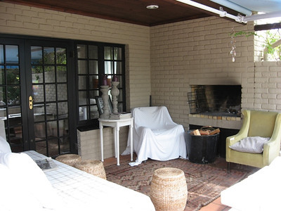 Partly covered porch with sofa and fireplace.