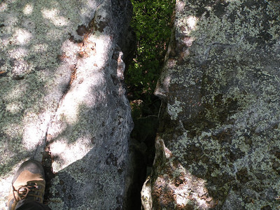 I am standing with one foot on each side of a crevice that has a long drop below me. Lost Overlook  Brady Mtn CT TN