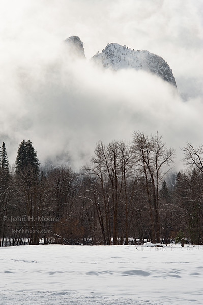 Granite peaks peaking through clouds above Yosemite Valley