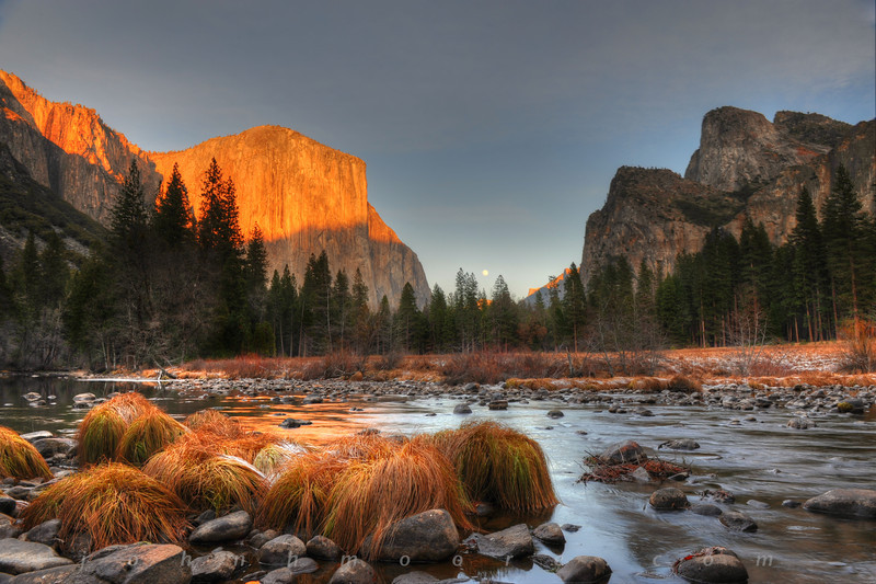 The full moon rises at sunset to the right of El Capitan, across the Merced River, on a frosty winter evening in Yosemite National Park