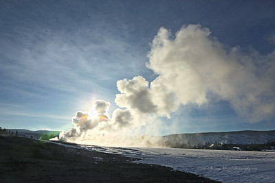 Old Faithful eruption with only a healthy amount of steam still rising from the vent with a sunburst breaking thru the steam cloud.