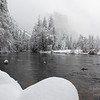 El Capitan looms through the falling snow over the Merced River in Yosemite National Park.