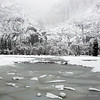 Upper Yosemite Falls looms in the snowfall above broken ice in flooded Cook's Meadow.  Yosemite National Park.