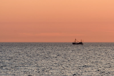 Fishingboat at sunset as seen from the beach of Katwijk.