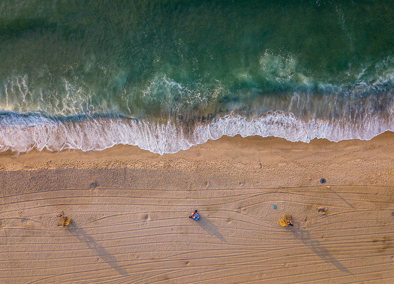An Aerial View Of Lifeguard Stand Shadows and Tractor Lines In The Sand and Gorgeous Green Ocean Waves 7/3/20