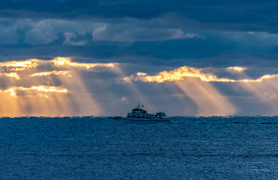 A Fishing Boat Passing In Front of Sun Rays Breaking Through The Clouds 10/18/18