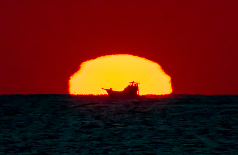 A Boat Passing In Front Of The Rising Sun 11/21/20