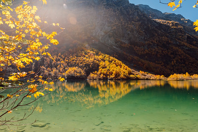 Mountain lake with transparent water and colorful autumnal trees. Mountains and scenic lake