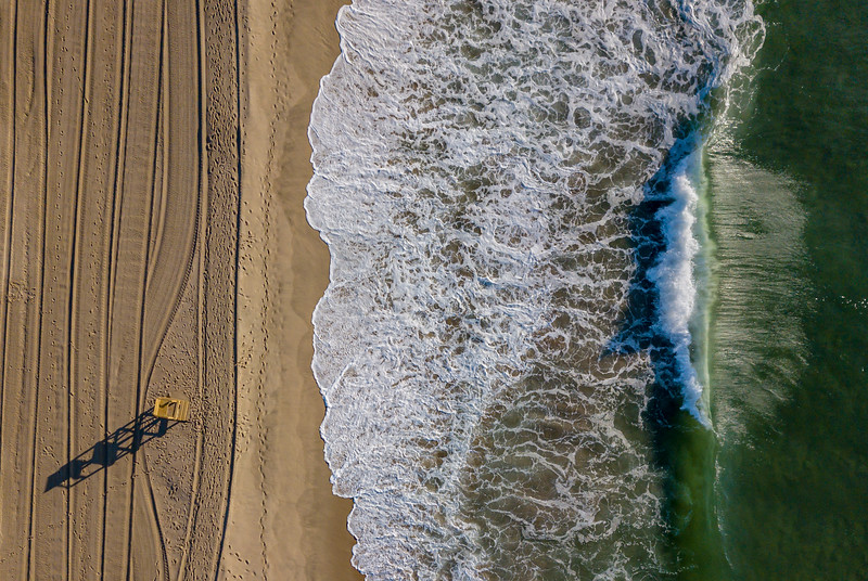 An Aerial View Of Lifeguard Stand Shadows and Tractor Lines In The Sand and Gorgeous G